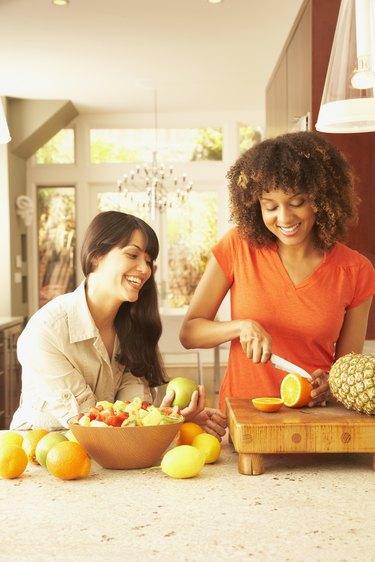 Multi-ethnic female friends cutting fruit
