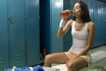 Young woman drinking in the locker room