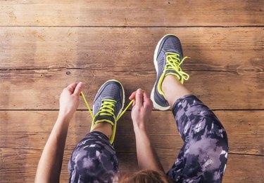 Unrecognizable young runner tying her shoelaces. Studio shot on wooden floor background.