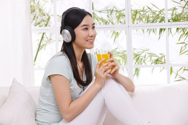 Young woman drinking juice and listening to music