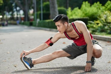 Asian young jogger stretching his legs outdoors