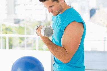 Sporty young man with dumbbell in gym
