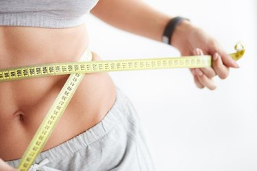 Bright closeup of slim young woman measuring her thin waist with a tape measure on white background