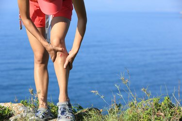 young sporty woman hold her sports injured leg