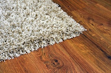 Parquet floor of the brown wooden planks and white shaggy carpet