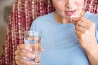 Pregnant woman taking a vitamin tablet