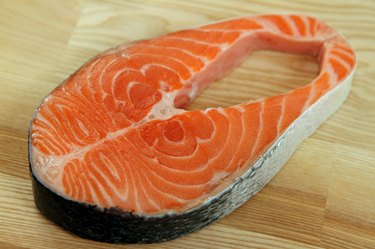 Close-up salmon steak on wooden plate