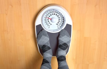 Male anorexic weighing himself