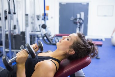 Concentrated woman lifting weights