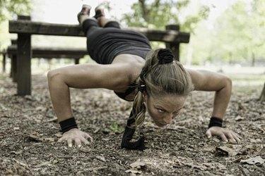 Female athlete doing push ups on fitness trail in park