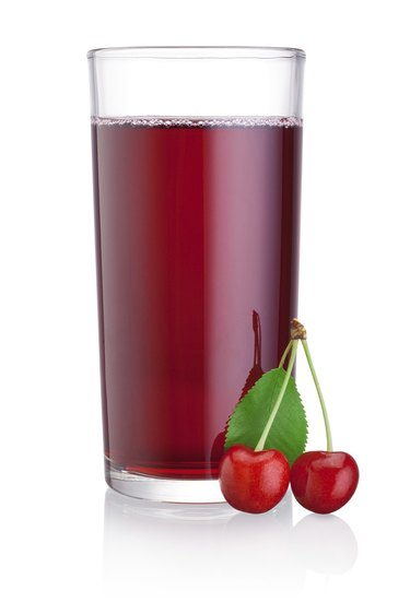 Glass of cherry juice with fruits isolated on white background