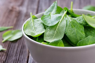 Fresh young leaves of spinach in bowl