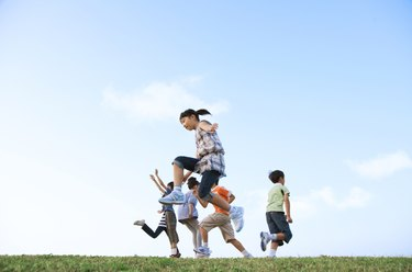 School children jumping at riverbank, copy space
