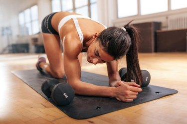 Young woman relaxing after doing pushups, woman exercising on fitness mat with dumbbells in gym.