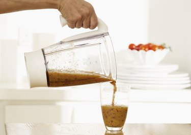 Woman pouring smoothie into glass, close up