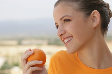 Young woman smiling with orange in her hand