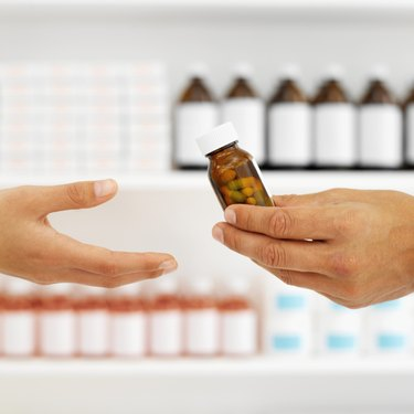 Close up of the hands of a pharmacist giving a patient a bottle of pills