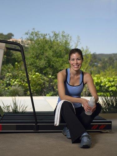 Woman sitting on treadmill