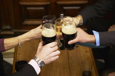 Five colleagues toasting each other with drinks in bar, close-up