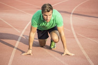 Male sprinter in clothes at start position, on red track.
