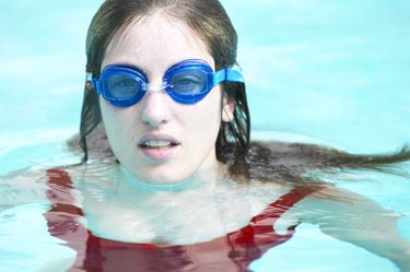 Girl in swimming pool and wearing goggles