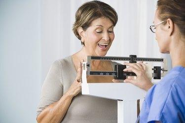 Senior Hispanic woman on medical scale