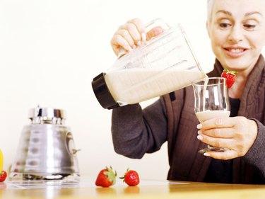 Senior woman pouring fruit smoothie