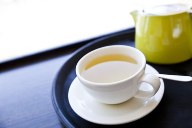 Cup of Green Tea on a tray with saucer and spoon