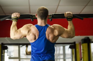 Professional bodybuilder with ideal muscular body doing pull-ups in the gym