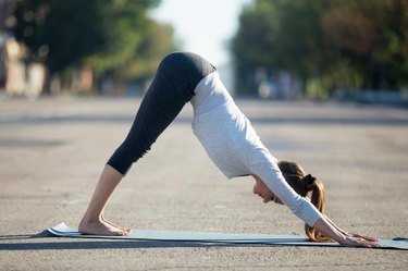 Yoga in the city: beautiful young sporty woman wearing sportswear working out on the street on summer day, doing downward facing dog posture, full length, profile view