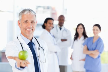 Mature doctor holding an apple while his medical team is looking at him