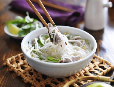 a bowl of pho with noodles and beef