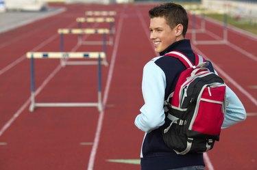 teenage boy (16 -18) wearing a backpack walking on a running track