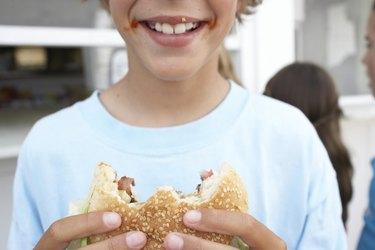 Boy (9-11) holding hamburger with 'bites' missing, smiling, close-up