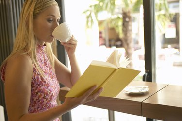 Young woman reading book in cafe, drinking from cup