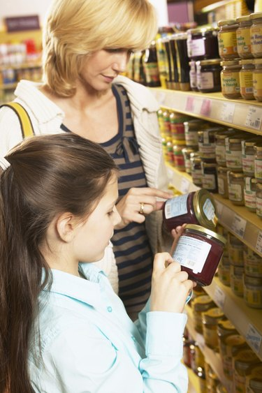 Mother and daughter (8-10) checking label on jars in supermarket