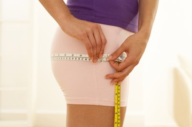 Woman measuring hips with tape measure