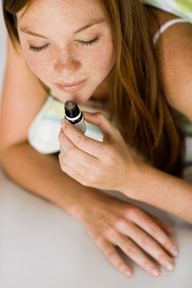 Young woman with small bottle of essential oil