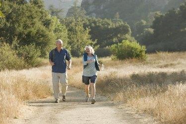 Mature couple walks down a nature trail.