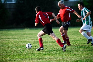 Soccer players chasing ball in game