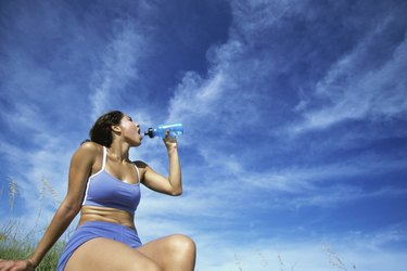 Low angle view of a young woman drinking water from a bottle