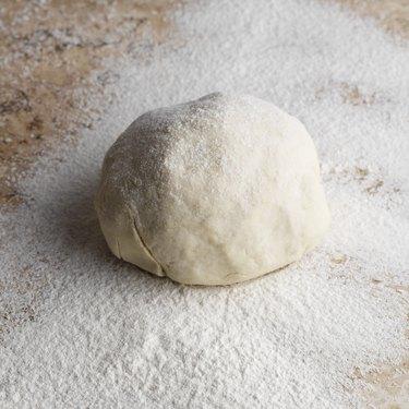 Ball of dough on floured countertop