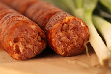 Delicious pork sausage with onion on wooden plate