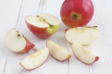 Pink lady apples cut on a white rustic wood table.