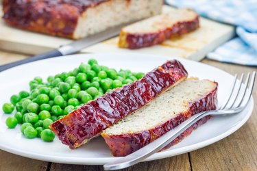 Homemade meatloaf garnished with green peas on a white plate