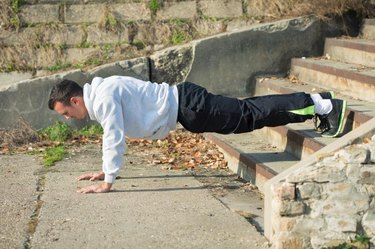 Attractive young man is exercising outdoors. He is doing push-ups on the staircase.