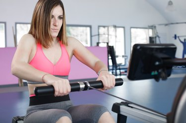 young woman exercising at the gym doing some pulls