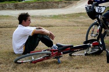 Boy sitting next to bmx bike
