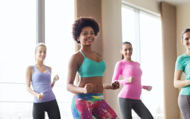 group of smiling people dancing in gym or studio