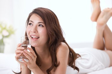 Young lady drinking water on bed